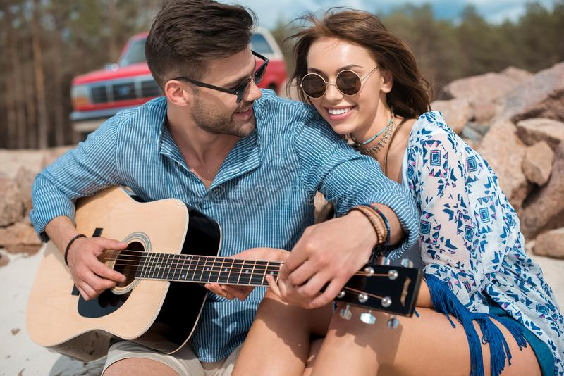 Happy couple hugging while man. Playing acoustic guitar royalty free stock images