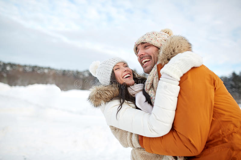 Happy couple hugging outdoors in winter royalty free stock images
