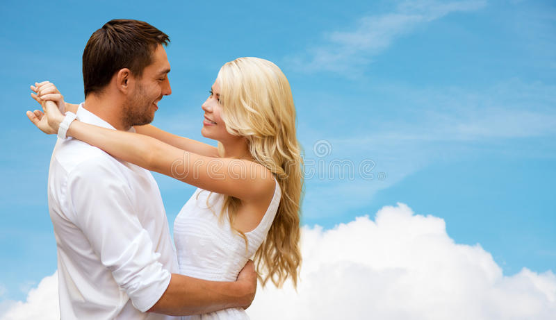 Happy couple hugging over blue sky and cloud stock photo