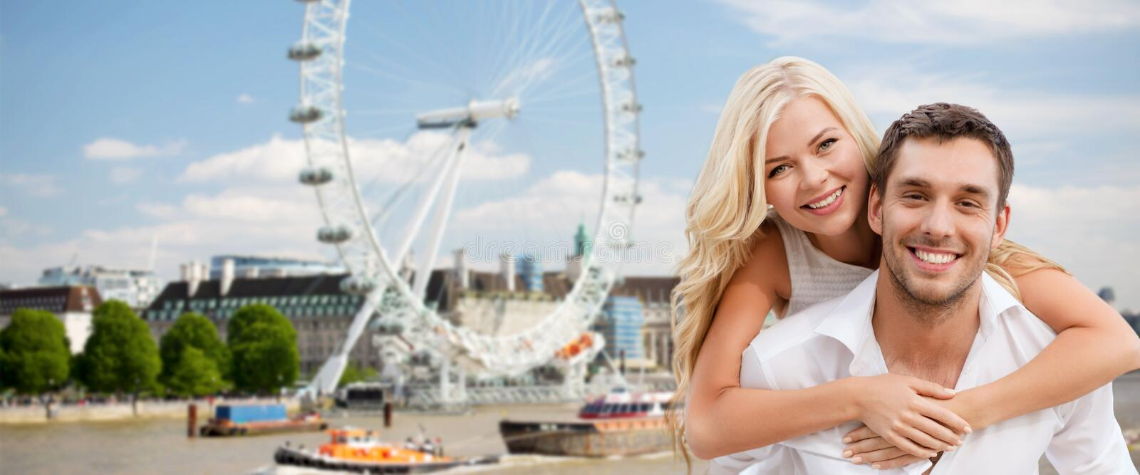 Happy couple hugging over london ferry wheel royalty free stock image