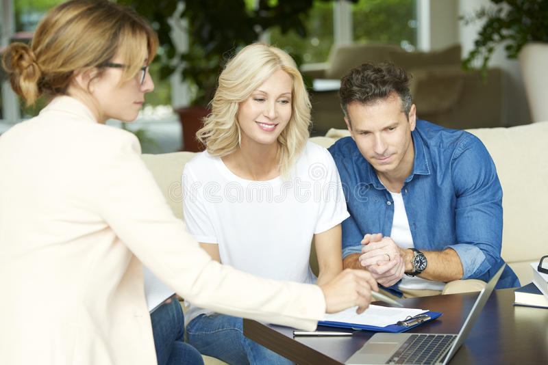 Happy couple with investment advisor stock image