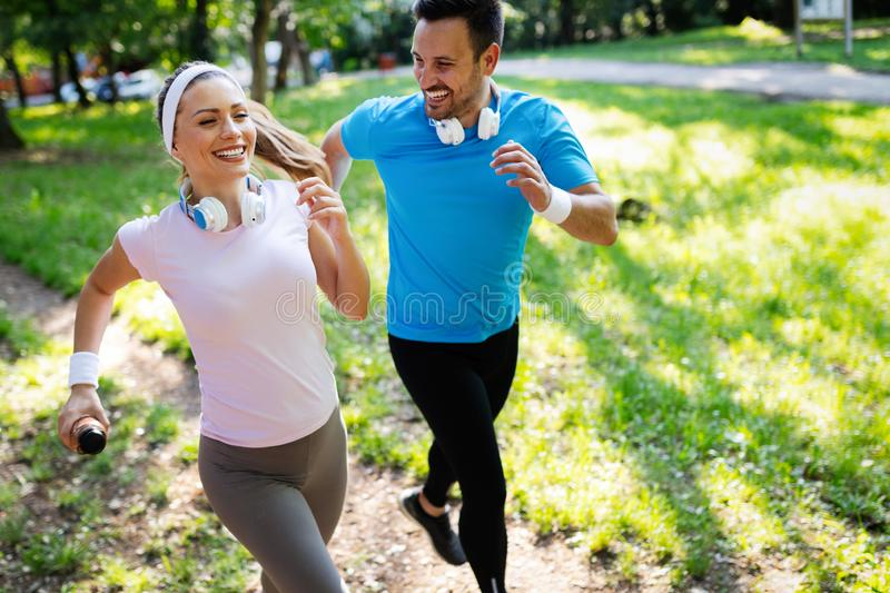 Happy couple jogging and running outdoors in nature stock images