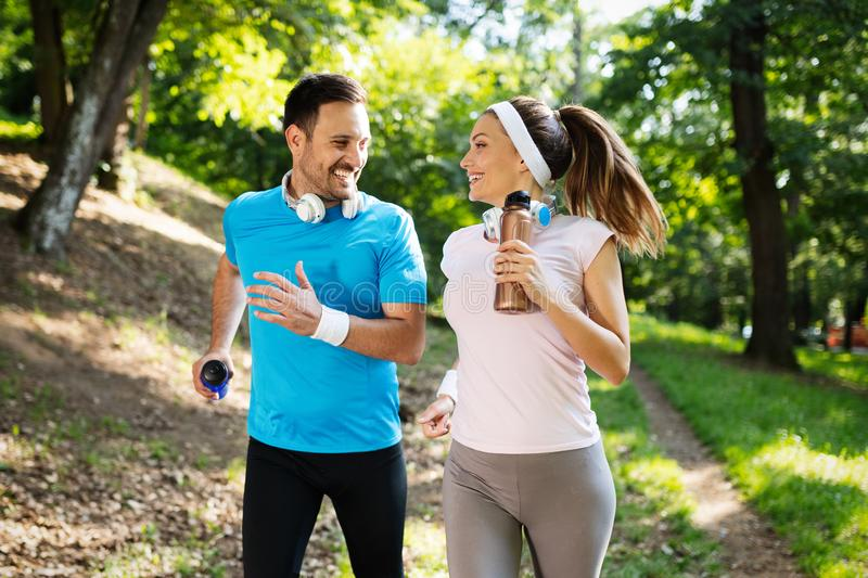 Happy couple jogging and running outdoors in nature stock image