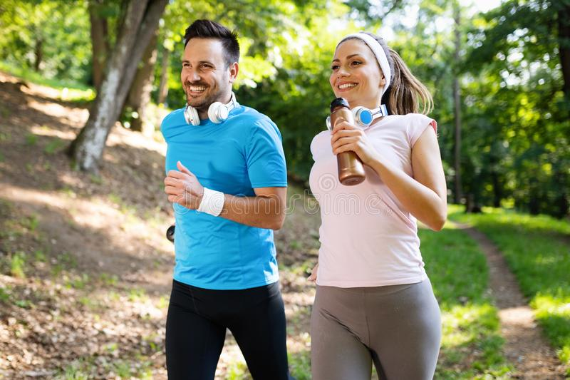 Happy couple jogging and running outdoors in nature royalty free stock images