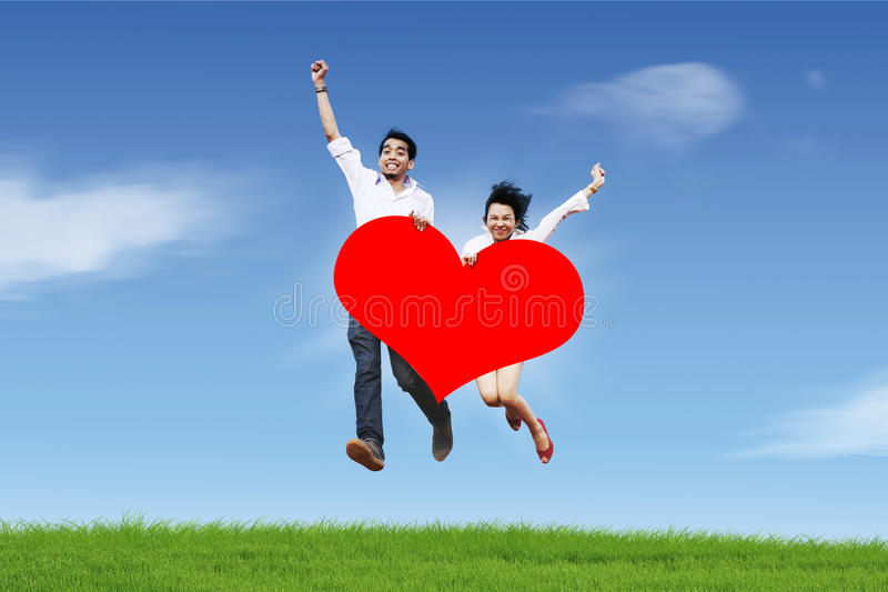 Happy couple jumping against blue sky