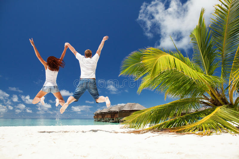 Happy couple jumping in the beach stock images
