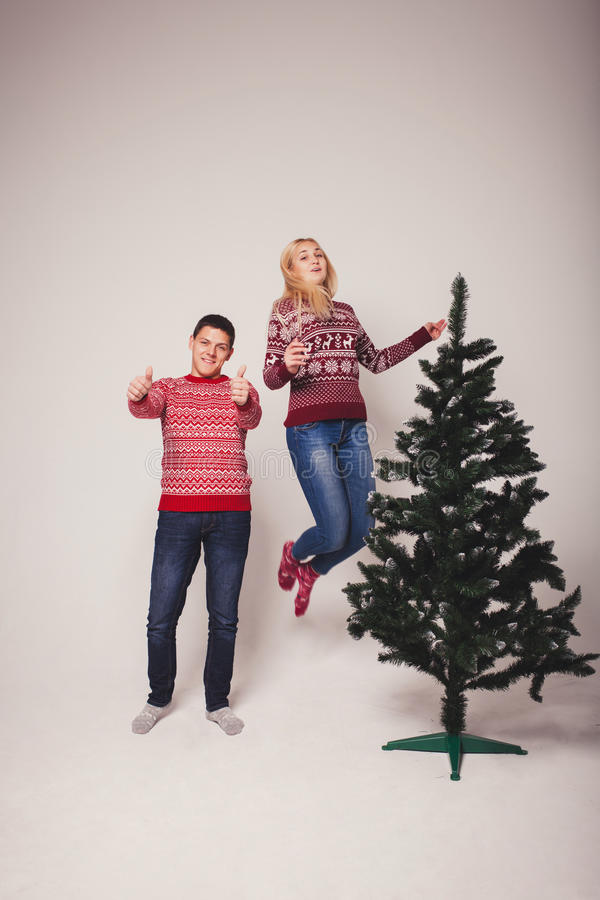 Happy couple jumping near the Christmas tree stock images