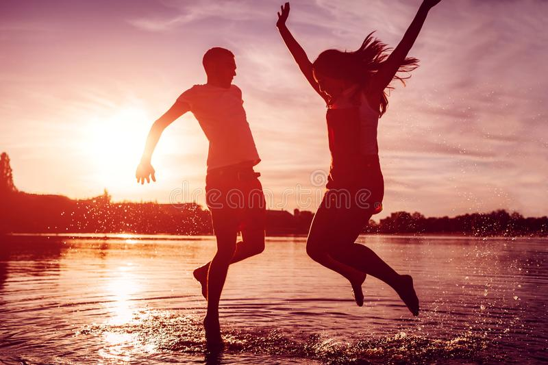Happy couple jumping on summer river bank. Young man and woman having fun at sunset. Guys hanging together stock photography