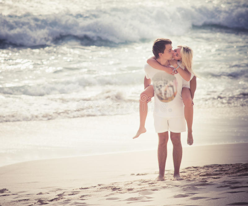 Happy couple just married and kissing at beach stock images