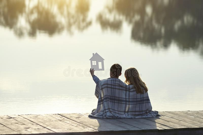 Happy couple of kids dream of a home. House concept stock photos