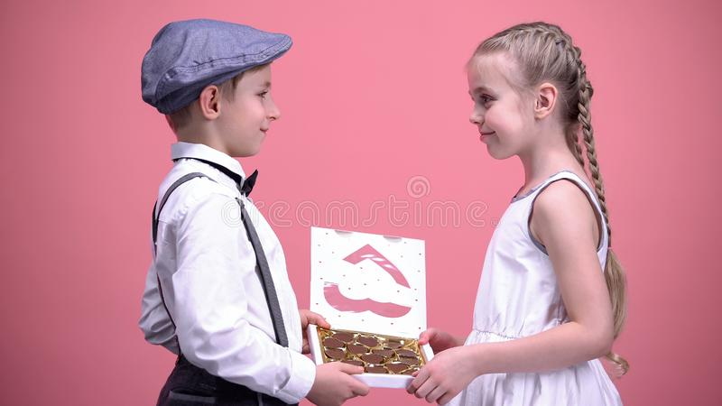 Happy couple of kids eating chocolate candies together, romantic date, love royalty free stock images