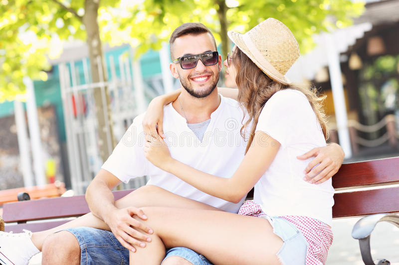Happy couple kissing on a bench royalty free stock photos