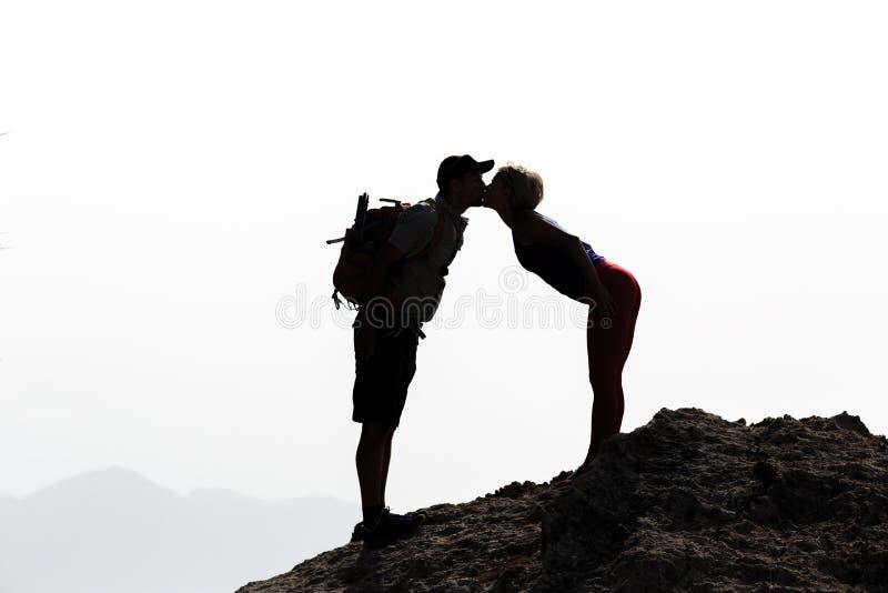 Happy couple kissing on mountain summit royalty free stock photos