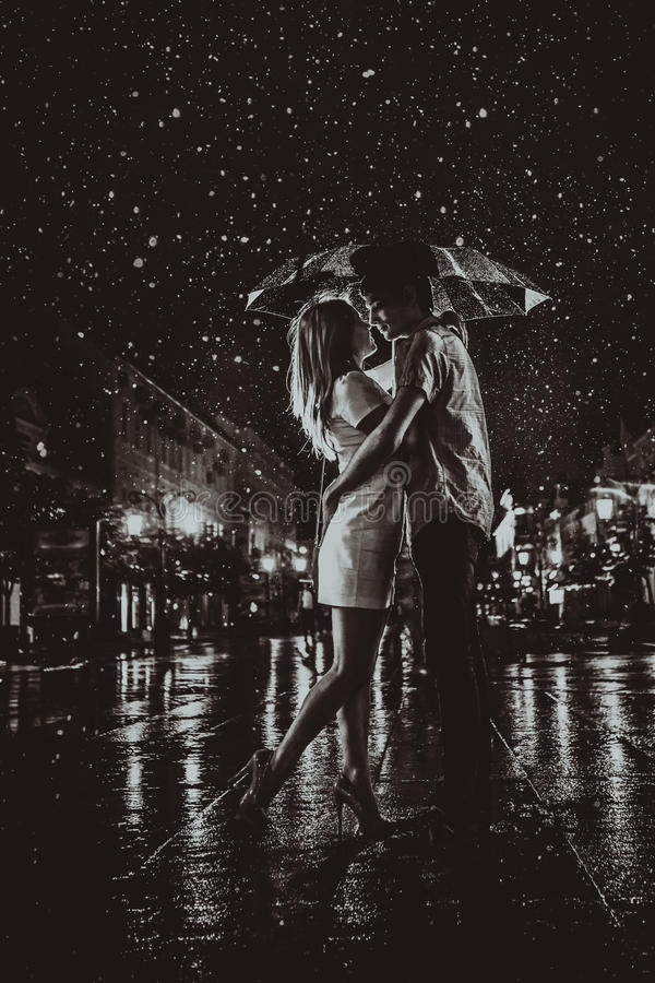 Happy couple kissing under the rain royalty free stock photography