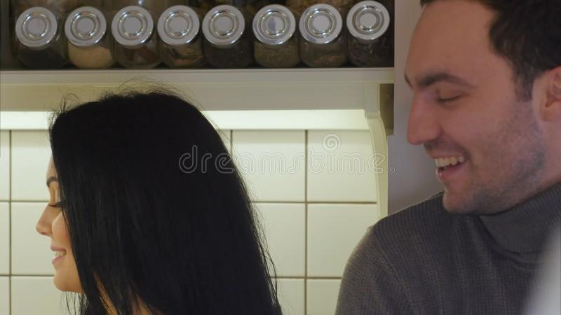 Happy couple on the kitchen washing vegetables to prepare healthy dinner and talking stock photography