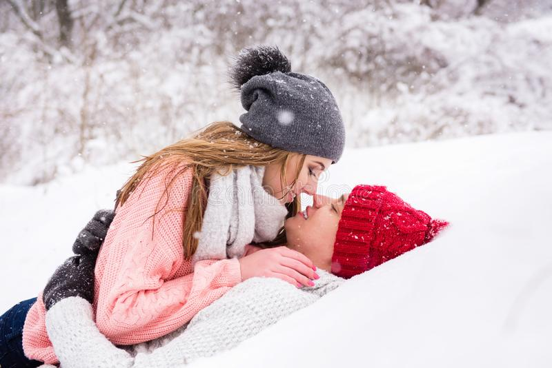 Happy couple lay down and kissing in snow stock image
