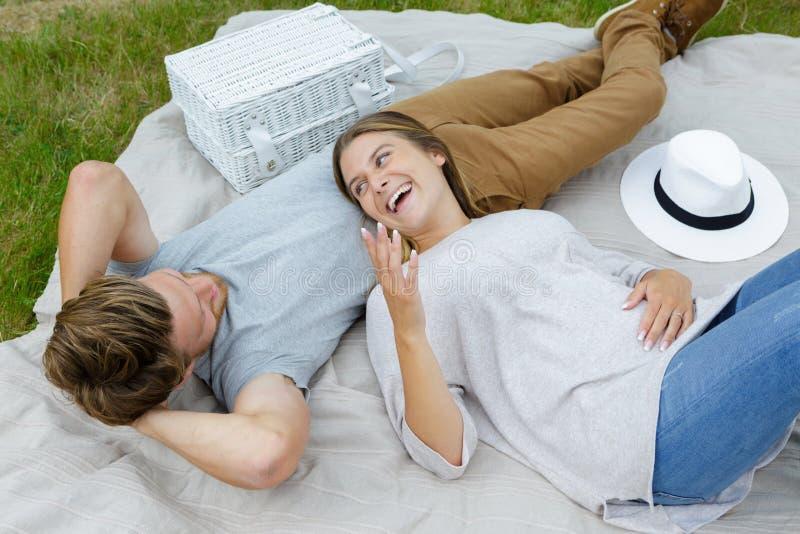 Happy couple lay on grass stock photo