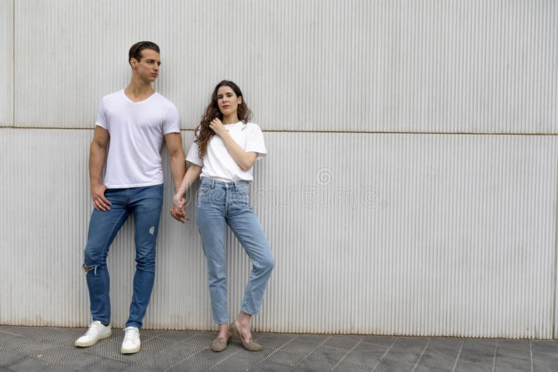Happy Couple Leaning Against Wall Holding Hands wearing casual clothes in a bright day stock image