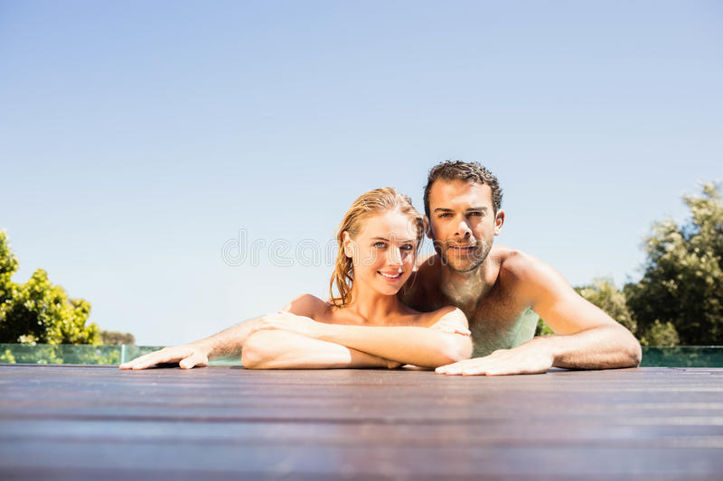 Happy couple leaning on pool edge. And looking at the camera stock photography
