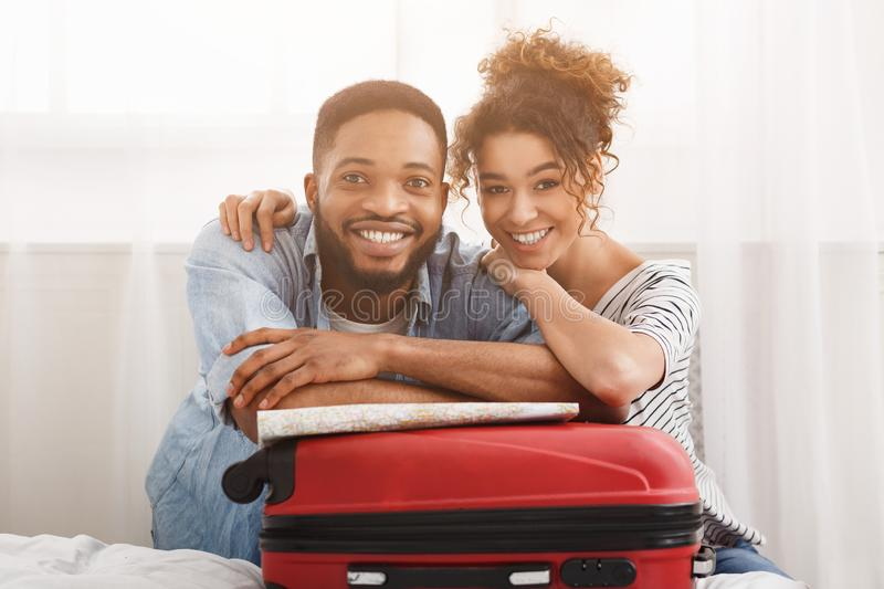Happy couple leaning on suitcase, preparing for vacation stock images