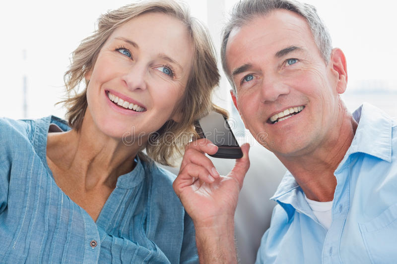 Happy Couple Listening To Mobile Phone Together Stock Photos