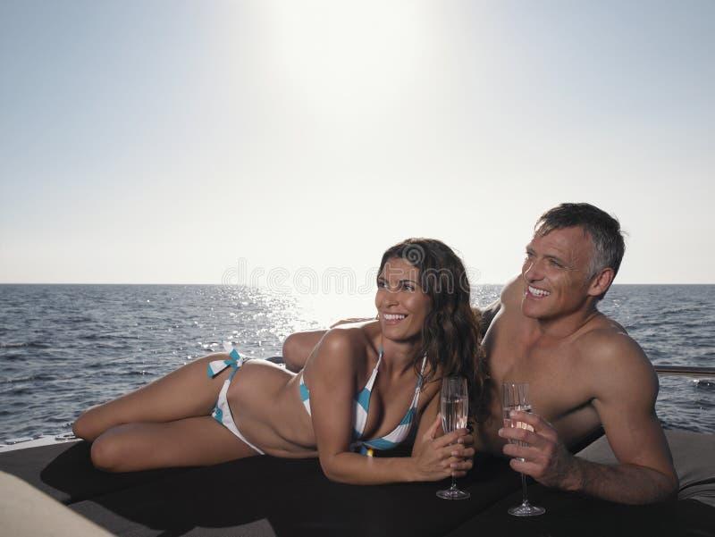 Happy Couple Looking Away While Lying On Yacht Stock Photo