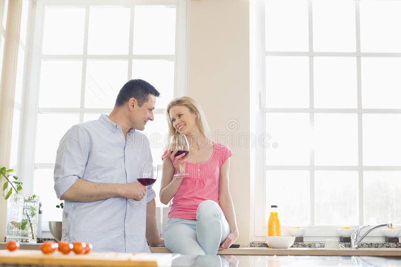 Happy couple looking at each other while drinking red wine in kitchen stock image