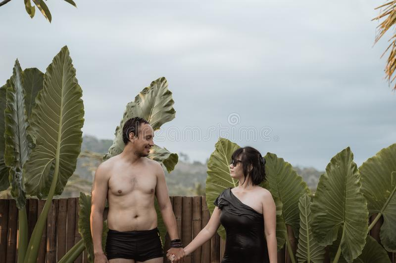 Happy couple looking each other with holding hands standing side the pool. Wearing swimming suit with natural background stock photo
