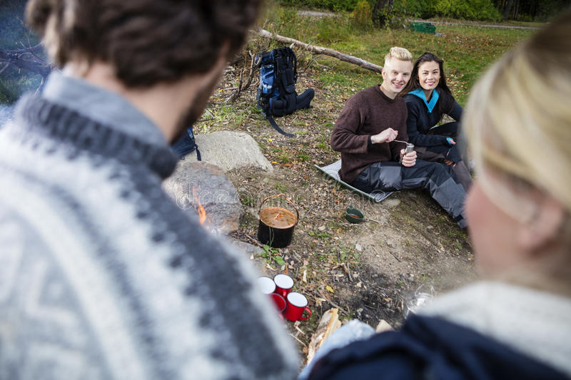 Happy Couple Looking At Friends During Camping royalty free stock photography