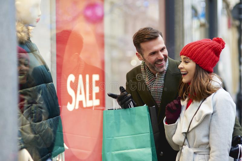 Happy couple looking at shop window with clothing stock photo
