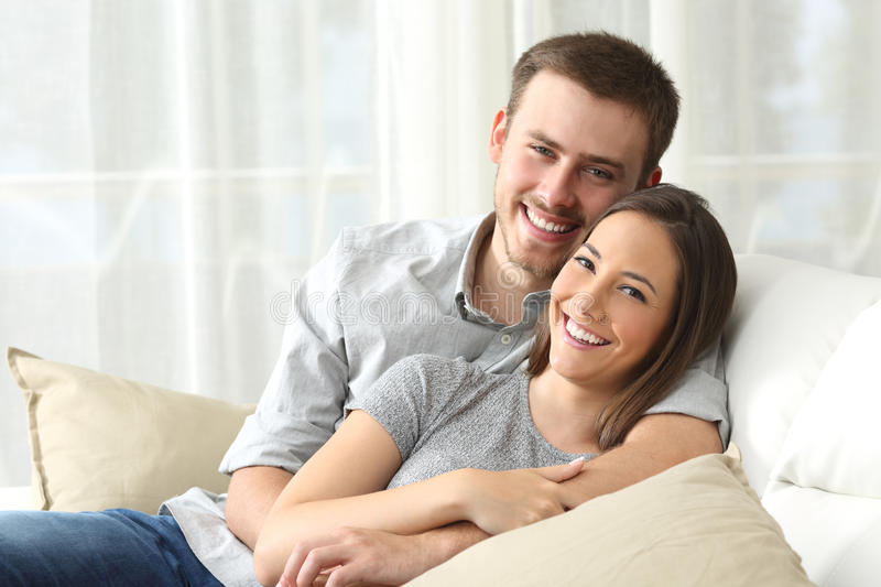 Happy couple looking to camera at home stock image