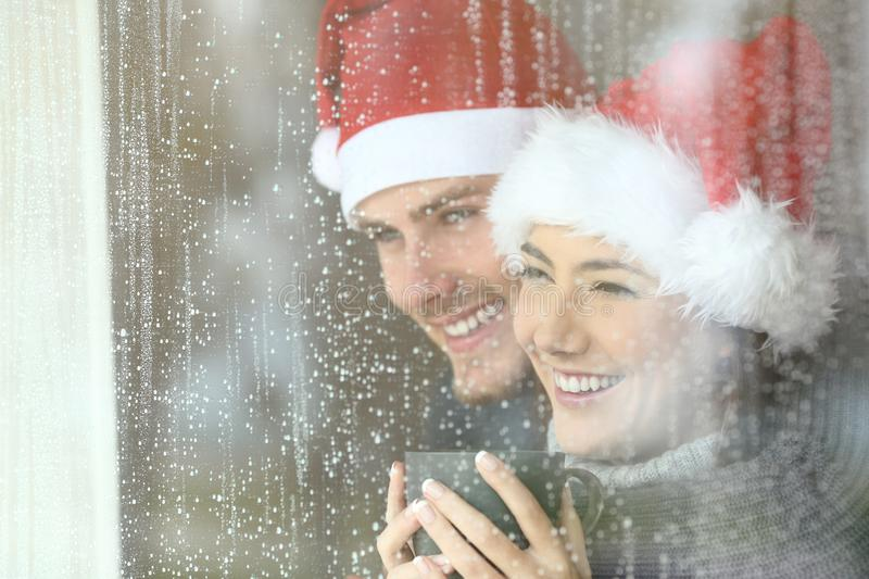 Couple looking through a window in christmas. Happy couple looking through a window at home or hotel in christmas stock photo