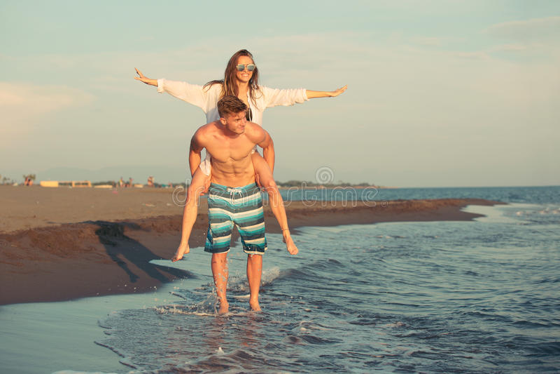 Happy couple in love on beach summer vacations. Joyful girl piggybacking on young boyfriend having fun stock photography
