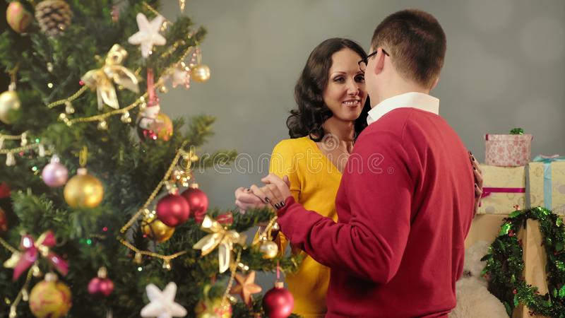 Happy couple in love dancing near Christmas tree, celebrating New Year together royalty free stock photos