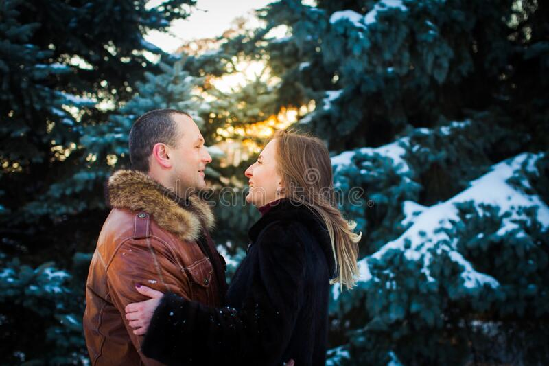 Happy couple in love embrace in snowy winter cold forest. Love and relationship concept royalty free stock images