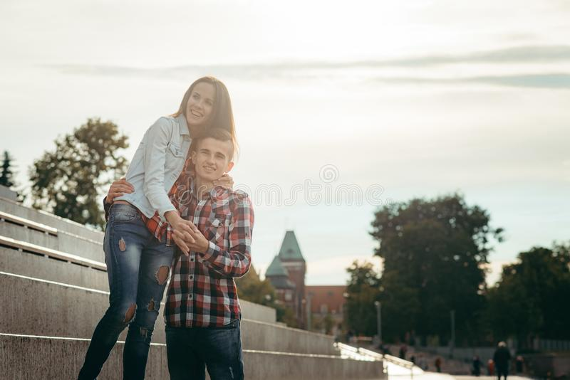 Happy couple in love. Emotional portrait. They are hugging in the sunny street. stock photos