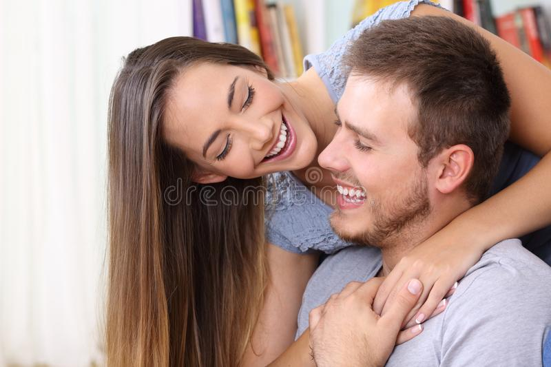 Happy couple in love flirting at home. Happy couple in love flirting looking each other at home royalty free stock images