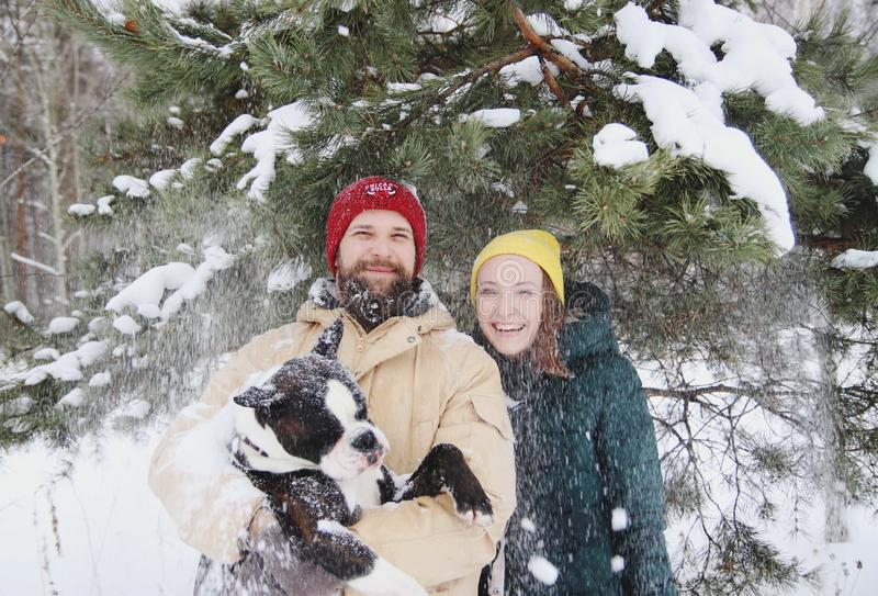 Happy couple in love having fun in the snow with his baby dog stock photos