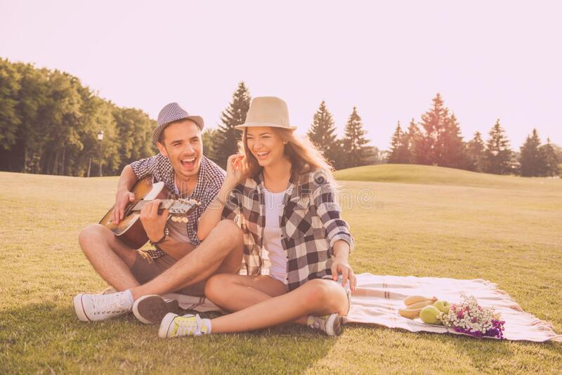 Happy couple in love having picnic in park with guitar stock photo