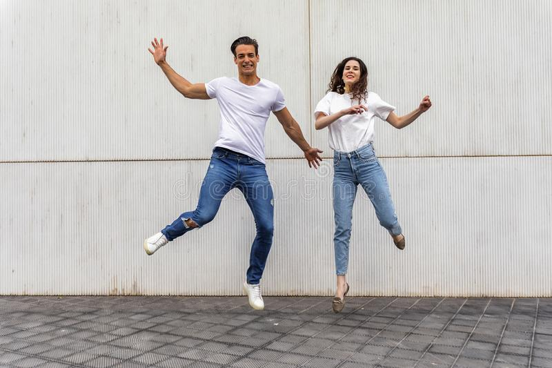 Happy couple in love jumping against grey wall royalty free stock photos