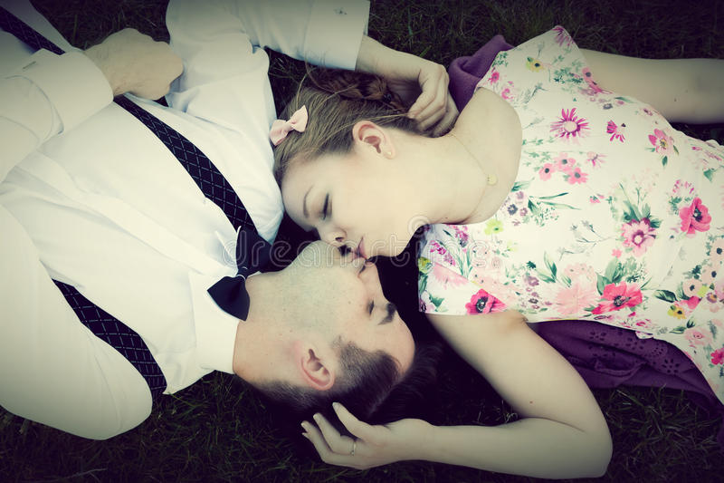 Happy couple in love kissing while lying on summer grass. View from above. Vintage royalty free stock images