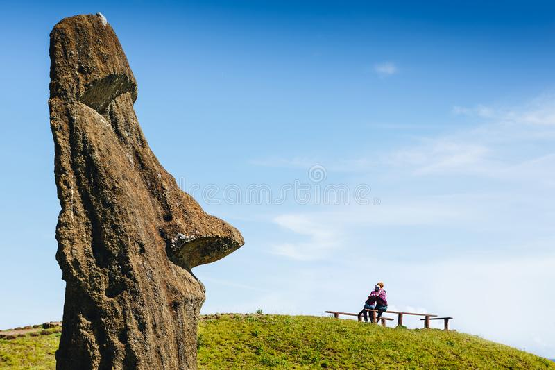 Happy couple in love and Moai statues in the Rano Raraku Volcano royalty free stock images
