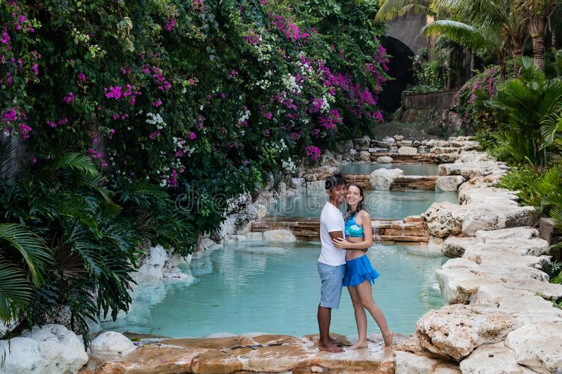 Happy couple in love. Multiethnic couple at the swimming pool. Swimming pool surrounded by pink bougainvillea flowers stock photos
