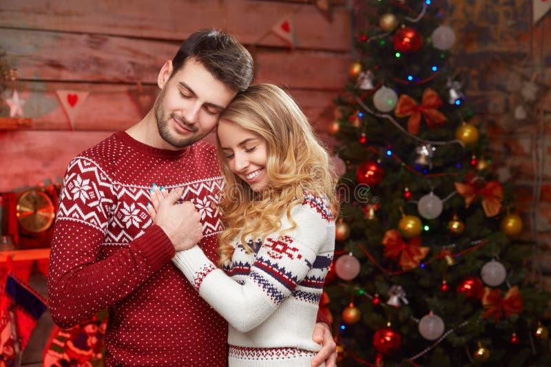 Happy couple in love over christmas tree stock photo