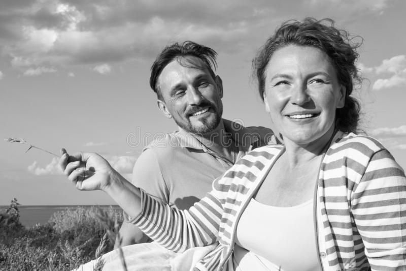 Happy couple in love at a picnic. Romantic concept at the beach. Cheerful couple having fun on summer vacation stock photo