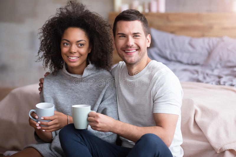 Happy couple in love sitting close to each other stock photos
