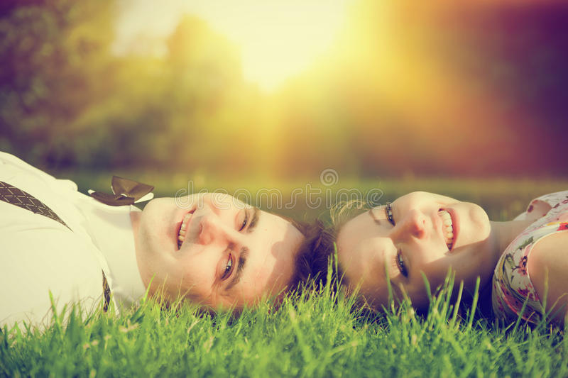 Happy couple in love smiling while lying on summer grass. Dating, romantic mood, sun light royalty free stock photo
