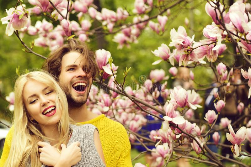 Happy couple in love in spring magnolia flowers. Spring. happy couple in love in spring magnolia flowers, smiling men and girl in garden with blossom tree stock images