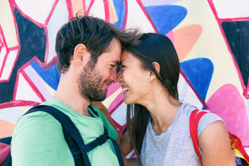 Happy couple in love taking a selfie doing funny kissing pose at famous tourist attraction Berlin wall, Germany, Europe travel stock images