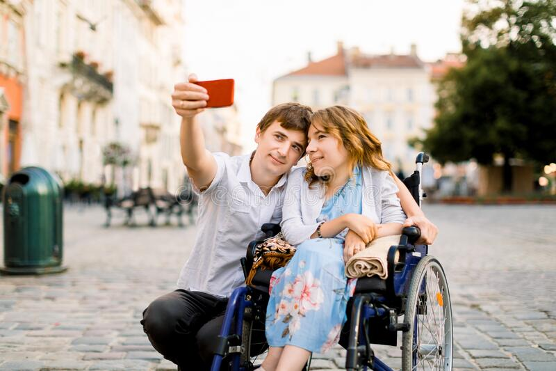 Happy couple in love taking selfie on the old city background - Disability concept with woman on wheelchair. Happy couple in love taking selfie on the old city royalty free stock photos